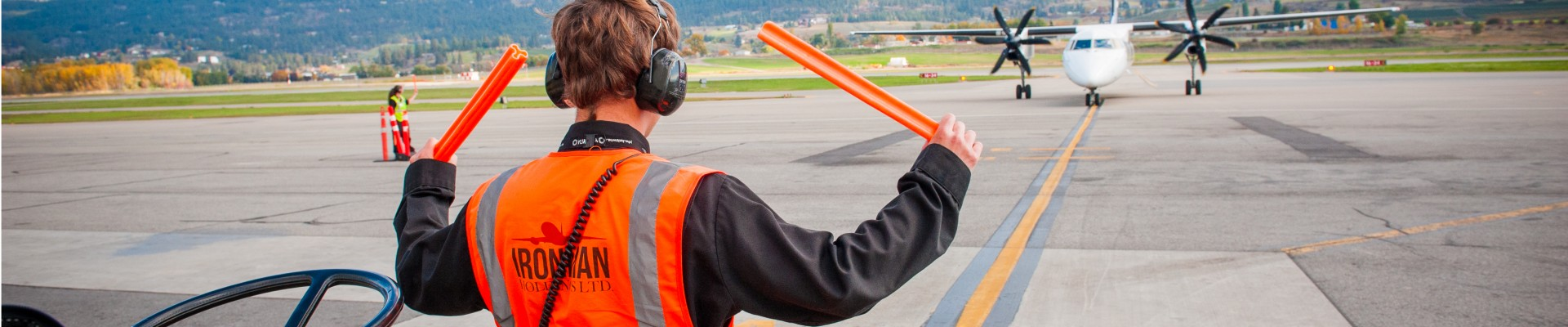 Airfield worker guides in a plane on a sunny day